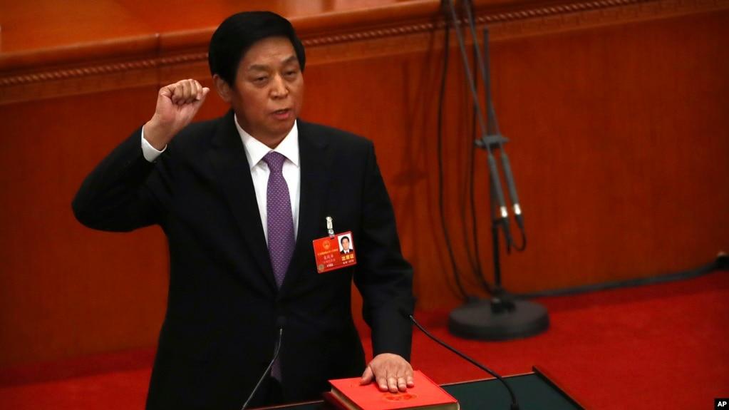 新当选的中国人大委员长栗战书2018年3月17日在全国人大全体会议上手按宪法,宣誓就职。