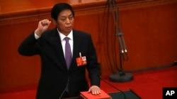 新當選的中國人大委員長栗戰書2018年3月17日在全國人大全體會議上手按憲法,宣誓就職。