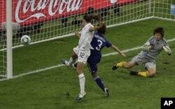 بازیکن امریکایی حین ضربه زدن به توپ که نمیتواند آنرا وارد دروازۀ جاپانی ها نماید.