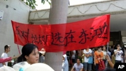 "Protesters hold up a banner which reads ""Against garbage incinerator along east river"" in Boluo county in south China's Guangdong province, Sept. 14, 2014."