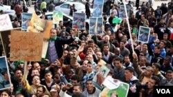 Pendukung pemerintah membawa poster pemimpin Muammar al-Gaddafi saat berkumpul menghadiri rapat umum pro-pemerintah di Tripoli, Rabu (2/16). Media pemerintah Libya tidak meliput protes-protes anti-Gaddafi yang berlangsung di berbagai tempat.