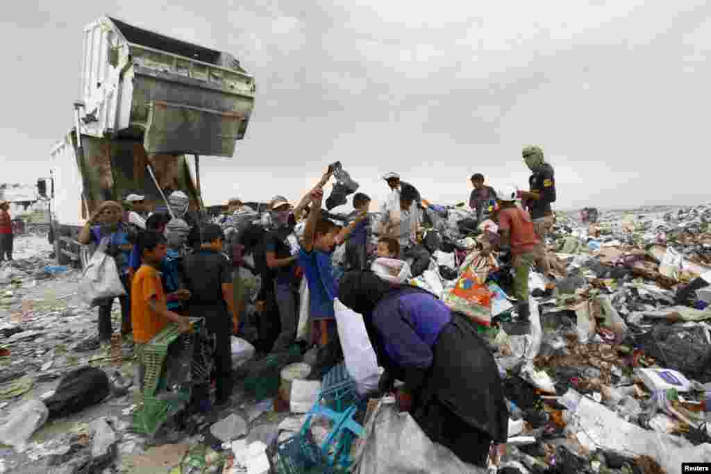 People collect garbage to be sorted and sold to nearby recycling centers in a district near Najaf, Iraq.