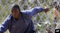 """A Zimbabwean man drops his hat as he flees across the border at Beitbridge Border Post in Musina, South Africa, Friday March 28, 2008. Once through the fence, the """"border-jumpers"""" make a dash across a narrow strip of tarmac, duck through some fencing, rip"""