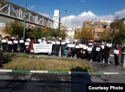 In this November 26, 2018 photo of protest by Iranian doctors outside parliament in Tehran, some protesters hold up a sign saying detained activist Farhad Meysami needs medical treatment at a well-equipped hospital.