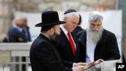 U.S. Vice President Mike Pence, center, looks at a book together with Western Wall Heritage Foundation Director General Mordechai Elias, right, and Rabbi of the Western Wall Shmuel Rabinovitch during a visit to the Western Wall, Judaism's holiest prayer site, in Jerusalem's Old City, Jan. 23, 2018.