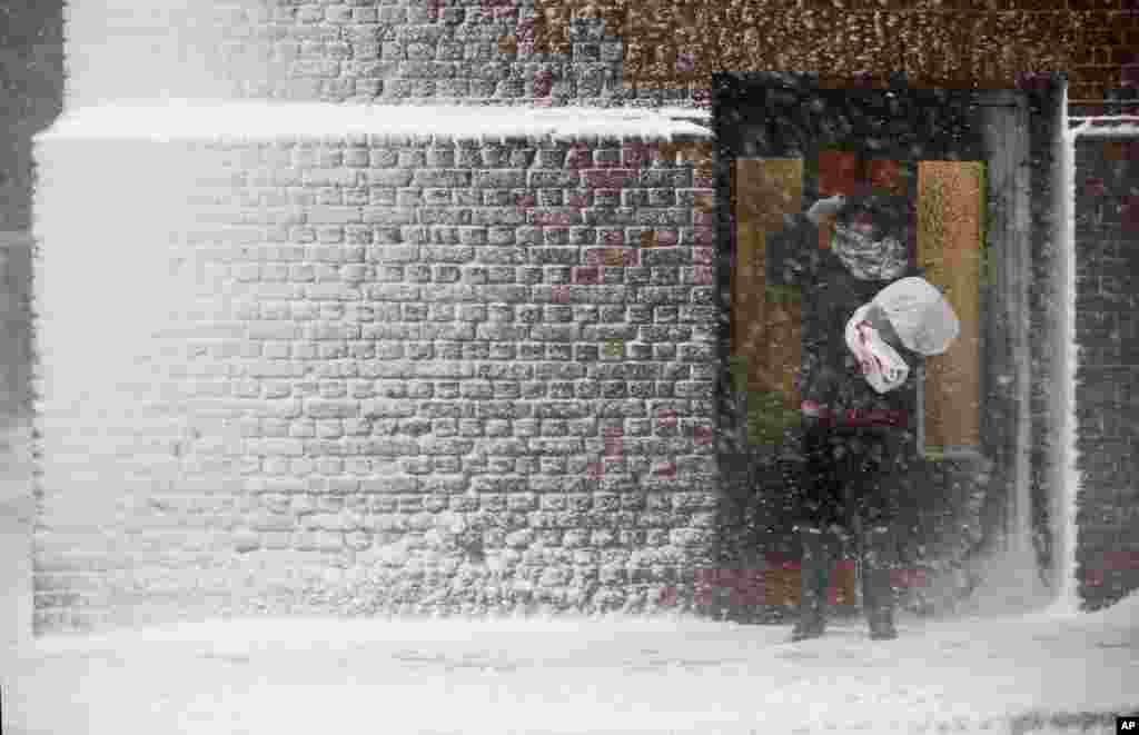 A person stands in the wind-driven snow during a winter storm in Boston, March 14, 2017.