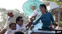 Lãnh tụ dân chủ Aung San Suu Kyi nhận được hoa từ người ủng hộ trên đường đi vận động tranh cử ở thị trấn Thone-Gwa ở Rangoon, Miến Điện, ngày 26/2/2012