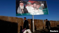 Men walk past a campaign banner of Afghan presidential candidate Abdul Rassoul Sayyaf, in Kabul, Feb. 9, 2014.