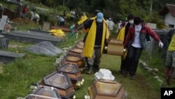 Wearing face masks to prevent infection, people carry a coffin containing the body of a landslide victim at a cemetery in Nova Friburgo, Brazil, 15 Jan 2011