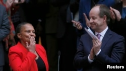 Outgoing French Justice Minister Christiane Taubira (L) reacts to her staff members near newly-appointed French Justice Minister Jean-Jacques Urvoas (R) during a handover ceremony at the Justice Ministry in Paris, Jan. 27, 2016.