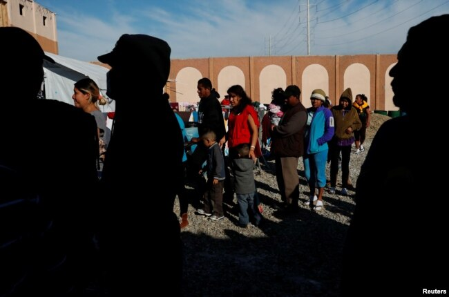 FILE - Migrants wait in line for food at a camp housing hundreds of people who arrived at the U.S. border from Central America with the intention of applying for asylum in the U.S., in Tijuana, Mexico, Dec. 12, 2018.