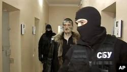 """俄羅斯電視網""""一頻道""""報道中顯示,烏克蘭安全局蒙面特工押送暗殺普京嫌疑人(中)"""