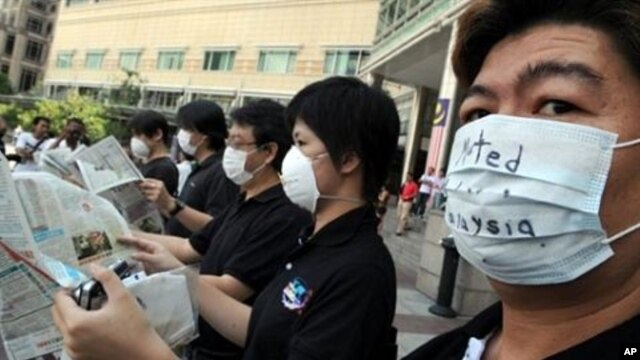 Activists wearing masks pretent to read newspapers upside down during a silent protest to support freedom of the press, outside a shopping mall in Kuala Lumpur (File Photo)