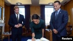 Pangeran Harry dari Inggris dan istrinya Meghan, yang sekarang bergelar Duke dan Duchess of Sussex, menandatangani buku tamu di kantor Taoiseach Leo Varadkar, pada awal kunjungan dua hari ke Dublin, Irlandia, 10 Juli 2018.