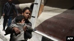 A Syrian boy carries a child while he runs for cover in the rebel-held area of Douma, east of the capital Damascus, as several air strikes pounded the city, April 22, 2015.