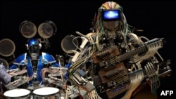 "Robot guitarist ""Mach"" and robot drummer ""Ashura"" (L), members of a robot rock band ""Z-Machines"", perform music during the two day art and technology event ""Maker Faire Tokyo."""