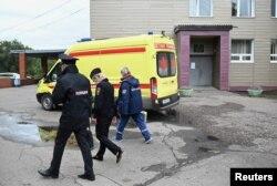 Un trabajador médico y agentes de policía caminan frente al Hospital de Emergencias Clínicas Número 1 de Oms la ciudad, donde ingresó el líder de la oposición rusa Alexei Navalny después de sufrir síntomas graves de envenenamiento según sus asesores.