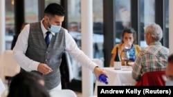 Seorang pelayan mengisi gelas di restoran seafood di Manhattan, New York City (foto: dok). Sektor jasa AS kembali bangkit dan mencatat rekor dalam bulan Juli.
