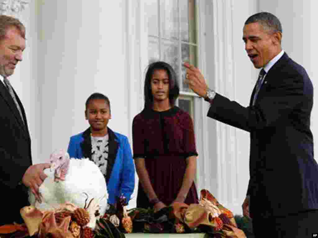 President Barack Obama, with daughters Sasha and Malia, pardons a turkey named Liberty a day before Thanksgiving. (AP)