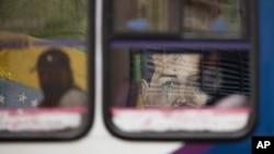 Un mural del presidente Nicolás Maduro enmarcado por una ventana de un autobús que pasaba en Caracas, Venezuela. Julio 22, 2020