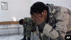 Two Libyan rebel fighters after their injured and killed colleagues were evacuated to the hospital of Ajdabiya, Apr 7 2011