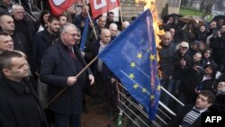 Serb ultranationalist leader Vojislav Seselj holds a burning European Union flag in front of the High Court building in Belgrade, March 10, 2016.