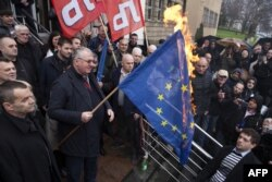 FILE - Serb ultranationalist leader Vojislav Seselj, center, holds a burning European Union flag in front of the war crimes court building in Belgrade, March 10, 2016.