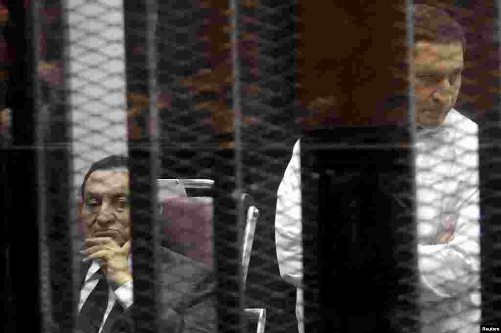 Egypt's ousted president Hosni Mubarak sits next to his son Alaa (right) inside a dock at the police academy, on the outskirts of Cairo, May 21, 2014.