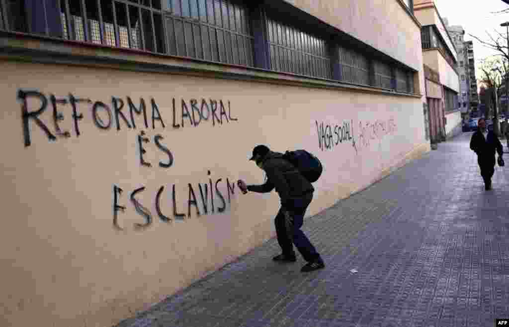 A demonstrator spraying graffiti in Barcelona, March 29, 2012. (AP)