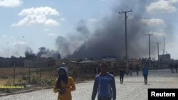 Plumes of smoke are seen behind buildings in Addis Ababa, Oromia,