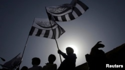 FILE - Supporters of the Jamaat-ud-Dawa Islamic organization are silhouetted against the sun as they raise their party flags while taking part in an anti-American rally in Lahore, May 25, 2012.