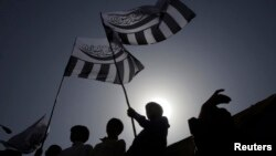 FILE - Supporters of the Jamaat-ud-Dawa Islamic organization are silhouetted against the sun as they raise flags while taking part in a rally in Lahore, May 25, 2012.