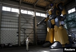 Sakakibara Kikai's engineer Go Sakakibara talks on a mobile phone to communicate with another engineer boarding the bipedal robot Mononofu during its demonstration at its factory in Shinto Village