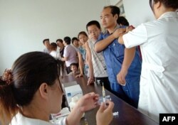 FILE - Residents queue up for their vaccine shots at a local hospital in Yuncheng, in northern China's Shanxi province.