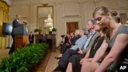 In this Sept. 19, 2014, sexual assault survivor Lilly Jay, right, listens to President Barack Obama, center, announce a 'It's On Us' campaign event in the East Room of the White House. (AP Photo/Pablo Martinez Monsivais)