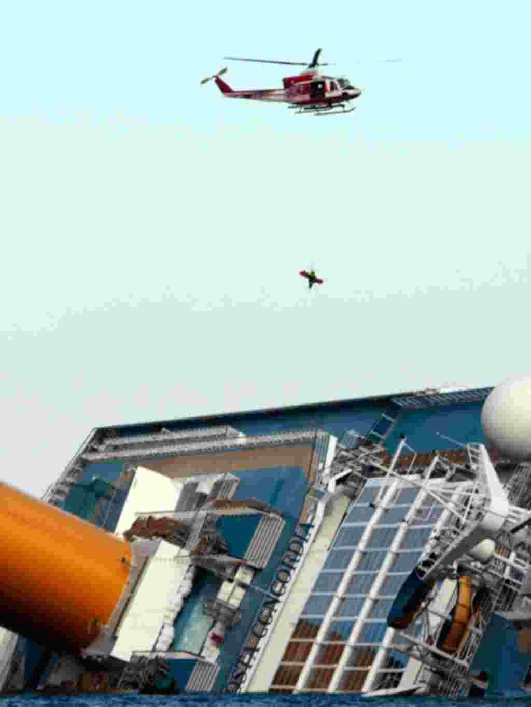 Helikopter pemadam kebakaran Italia menyelamatkan seorang penumpang dari kapal pesiar Costa Concordia, 15 Januari (AP).