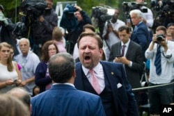FILE - Conservative radio host Sebastian Gorka yells at White House correspondent for Playboy magazine Brian Karem after President Donald Trump spoke about the 2020 census in the Rose Garden of the White House, in Washington, July 11, 2019.