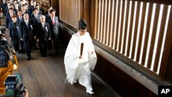 A group of Japanese lawmakers are led by a Shinto priest as they visit Yasukuni Shrine during the four-day annual Autumn Festival in Tokyo, Oct. 20, 2015.