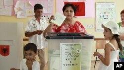 Seorang warga Albania tengah memasukkan surat suaranya di sebuah TPS di Tirana, Albania (23/6).