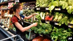 FILE - Crystal Dvorak shops at WinCo Foods, May, 7, 2021, in Billings, Mont. Dvorak was getting ingredients to make soup with potatoes and onions she got from a food bank after recently losing her job as an audiologist.