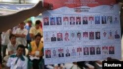 Warga menyaksikan penghitungan suara pemilu di sebuah TPS di Jakarta, Rabu (9/4).