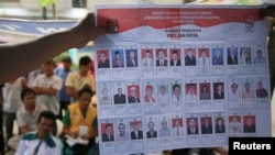 Warga menyaksikan petugas penghitungan suara saat memperlihatkan kertas-kertas suara di sebuah TPS di Jakarta (9/4).