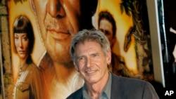 هریسون فورد در کنار یک پوستر فیلم ایندیانا جونز - آرشیو