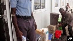 利比里亞衛生部副部長尼耶斯瓦(右)1月4日為世衛組織宣佈疫情前洗手資料照。