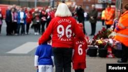 一名妇女与两个儿童在利物浦安菲尔德球场参加为1989年FA杯利物浦队和诺丁汉森林队半决赛期间96名球迷死亡而举行的追思会。(2016年4月15日)