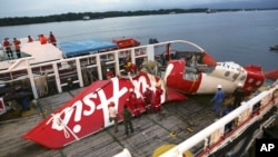 Crew members of Crest Onyx ship prepare to unload parts of AirAsia Flight 8501 from a ship at Kumai port in Pangkalan Bun, Jan. 11, 2015.