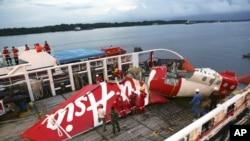 Các thành viên phi hành đoàn của tàu Crest Onyx chuẩn bị dỡ bỏ những bộ phận của máy bay AirAsia Flight 8501 từ một con tàu khác tại cảng Kumai ở Pangkalan Bun, ngày 11/1/2015.