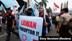 """Para pengunjuk rasa meneriakkan slogan-slogan saat aksi mendukung Komisi Pemberantasan Korupsi (KPK) di luar kantor KPK di Jakarta 8 Oktober 2012. Mereka mambawa spanduk bertuliskan, """"Lawan koruptor"""". (Foto: REUTERS/Enny Nuraheni)"""