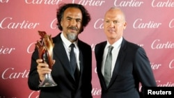 'Birdman' Director Alejandro Gonzalez Inarritu, left, holds his Director of the Year Award as he poses with actor Michael Keaton at the 26th Annual Palm Springs film festival in Palm Springs, Calif., Jan. 3, 2015.