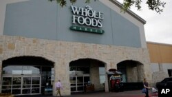 A shopper leaves a Whole Foods Market, June 16, 2017, in San Antonio, Texas.